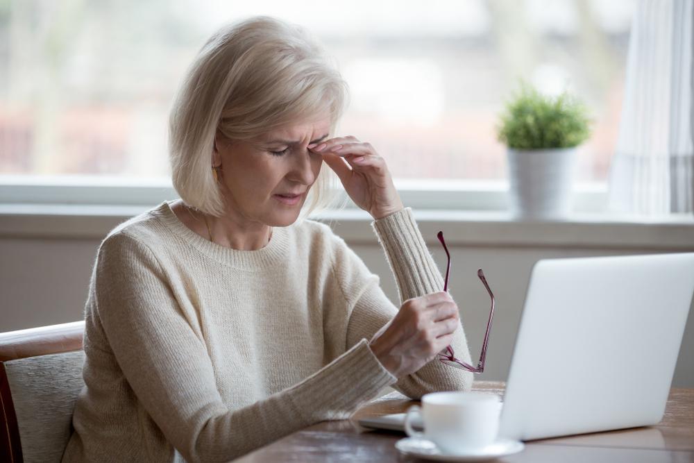 vrouw moedeloos achter laptop
